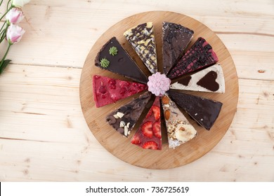 A wooden plate with different types of raw vegan cake in a little pastry.