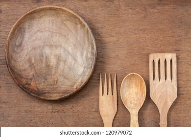Wooden plate, fork and spoon on oak wood texture background