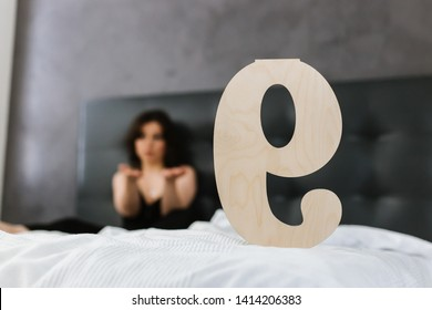 "A wooden plate with the inscription ""nine"" stands on the bed, a beautiful young Caucasian woman, Numerology, numbers"