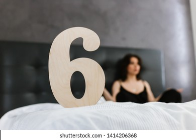 "A wooden plate with the inscription ""six"" stands on the bed, a beautiful young Caucasian woman, Numerology, numbers"