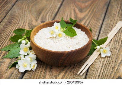 Wooden plate with jasmine rice and jasmine flowers on a wooden background