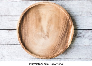 Wooden plate on wooden table background