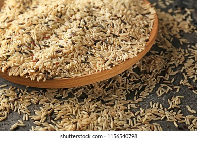 Wooden plate with raw rice on table, closeup