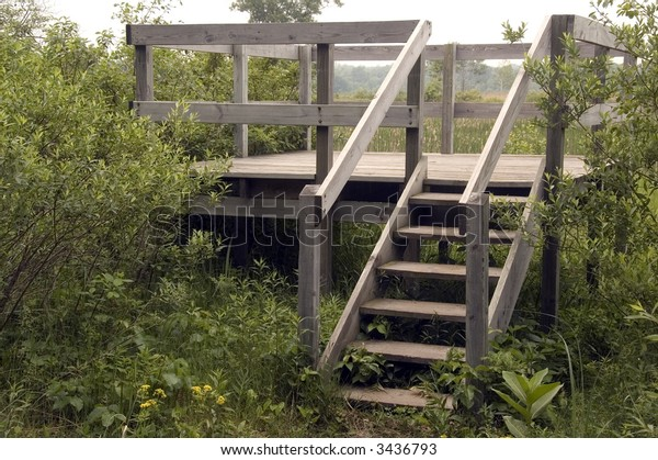 Wooden platform for birdwatchers by field and stream