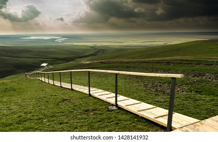 Wooden platform on a high hill in the steppes of Kalmykia. Spring landscape. Travels in Russia