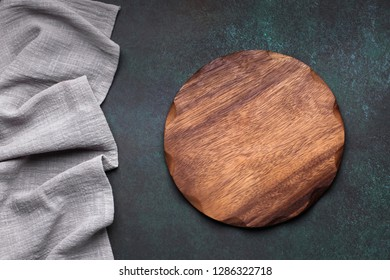 Wooden platter and napkin on dark background. Kitchen accessories for serve. Top view with copy space