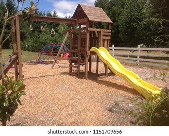 A wooden playhouse for children with a yellow slide, bright colored play equipment and landscaped surroundings. Backyard play structure with green background.