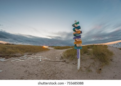Wooden pointer sign on the beach of the Baltic sea