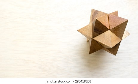 Wooden pointy cube puzzle on wooden surface. Concept of complex and smart logical thinking. Slightly defocused and close up shot. Copy space.
