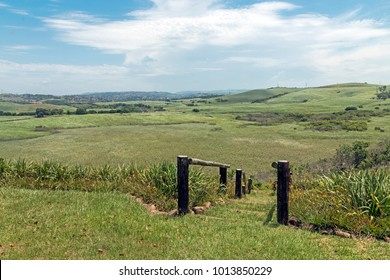 Wooden pole barrier fenced walkway , green vegetation and sugar cane plantations against distand Durban blue cloudy  skyline at Mount Moreland at Verulum in South Africa