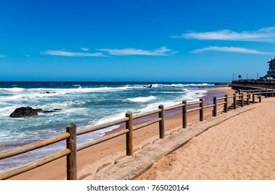 Wooden pole barrier on beachfront against beach sea and blue sky landscape at Mdloti in Durban, South Africa