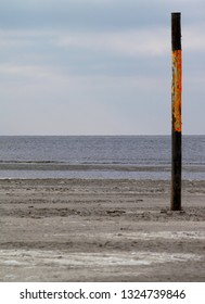 wooden pole in front of a calm sea