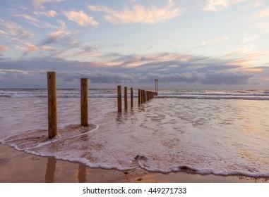 Wooden poles Aldinga silver sand beach sunset