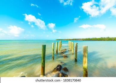 Wooden poles in beautiful Sombrero beach shore. Florida, USA