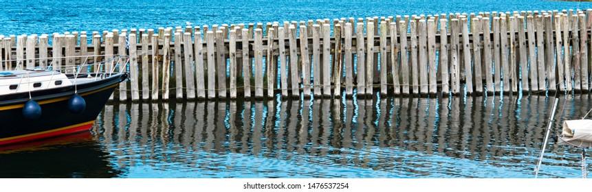 Wooden Poles, breakwaters, and detail of boat in lake called Veerse Meer. In Veere,  The Netherlands