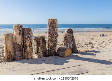 Wooden poles with fishing nets at the sandy beach on the coast n the Netherland