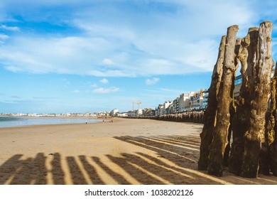 Wooden poles in foreground on coast and embankment with old and modern houses in background on bright sunny day in Saint-Malo, Brittany, France
