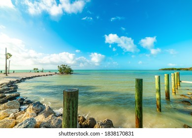 Wooden poles and turquoise water in beautiful Sombrero beach shore. Florida, USA