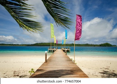 A wooden pontoon with beautiful colourful flags and palm tree leafs on one of the island of the mentawai in west sumatra, Indonesia