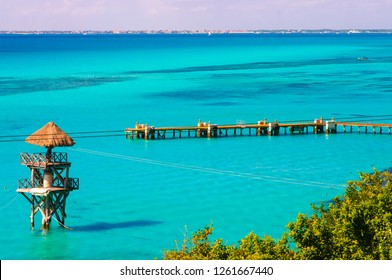 Wooden pontoon on the beautiful blue shades of the Caribbean sea, view from Isla Mujeres with Cancun coastline in the back