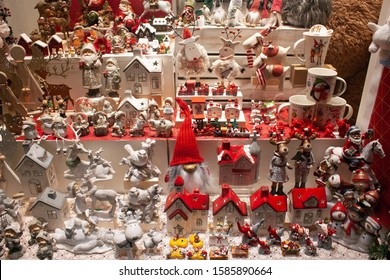 Wooden and porcelain Christmas multicolored decoration. Christmas dwarfs, kissing and hugging children, Santa Lucia, animals like moose, deers, bear and red-white decorative houses.