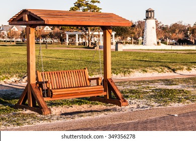 Wooden porch swing at Buckroe Beach in Hampton, Virginia with the lighthouse in the background.