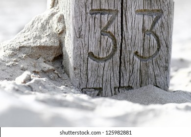 A wooden post at the beach in the Netherlands (Dutch seaside) indicating distance