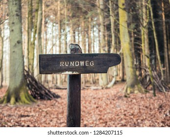 "Wooden Post indicating circular path in German (Letters saying ""Circular path"")"