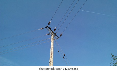 a wooden post on the top of which rest high voltage power lines against a blue sky.
