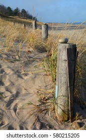 Wooden posts line a sandy beach in northern Michigan. On each post is a rock.  There is beach grass along the posts and Lake Superior is in the background.