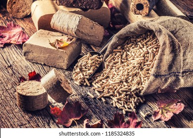 Wooden pressed pellets and briquettes from biomass with autumn leaves.