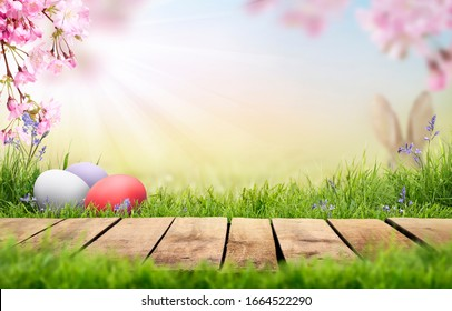 A wooden product display top with an Easter background of painted eggs, rabbit ears, green grass, meadows and pink cherry blossom flowers.