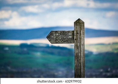 Wooden public footpath sign with hills and sky in the background on rural country walk Pendle Hill, England UK