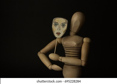 Wooden puppet doll on hinges holds a mask in hands and covers her face on a black background