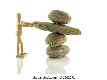 wooden puppet holding rocks isolated on white  in perfect balance
