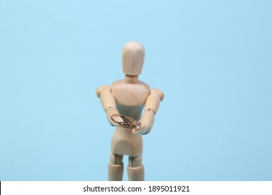 Wooden puppet holds a gold ring with a diamond. Marriage proposal