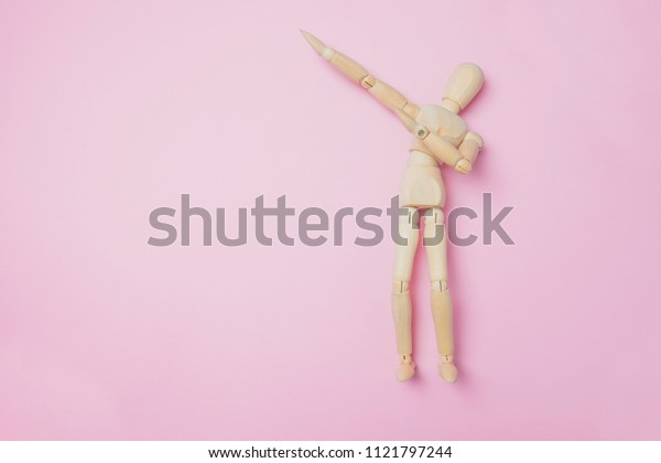 Wooden puppet points aside with its hand. Conceptual image about relax time. Minimal style.