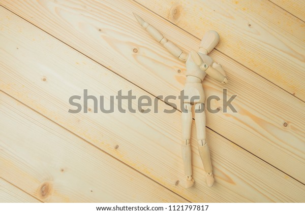 Wooden puppet points aside with its hand. Conceptual image about relax time on wood table.