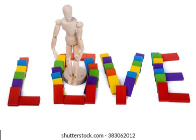 Wooden puppet standing in colorful domino which write love
