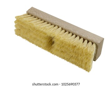 Wooden push broom head with yellow bristles on a white background