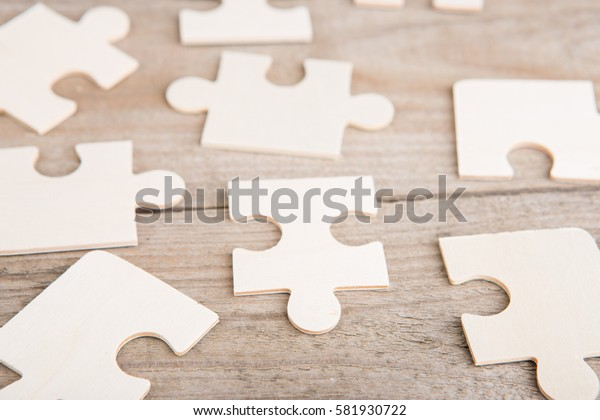Wooden puzzle pieces on a wooden background