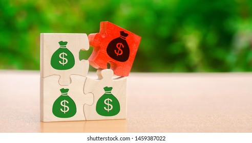 Wooden puzzles with the image of money. Withholding money and commission. Tax and taxation. The taxes burden. Net income. Costs. Ebitda. Business and Finance. Profit management. Investments