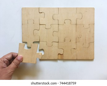 The wooden puzzles were almost complete. There is one remaining in the hand. The background is white.