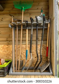 Wooden rack with different garden tools and equipment