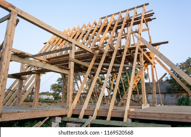 Wooden rafters of a new home under construction at sunset. New house construction interior with exposed framing.