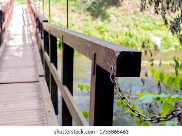 Wooden railing of a bridge over a small river. Close-up.