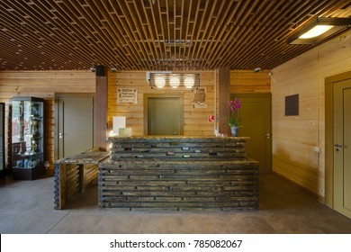 A wooden reception in the building of a sauna and flowers and lamps