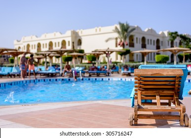 Wooden recliner chair standing on paving overlooking a resort swimming pool and the hotel building with additional chairs and umbrellas in the foreground for a relaxing vacation
