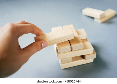 wooden rectangles, the female hand holds one rectangle. pyramid of rectangles on a white background