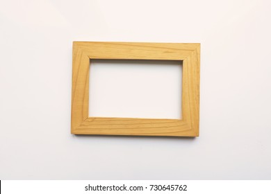 Wooden rectangular photo frame on white background. Close-up. Top view. Nobody, empty